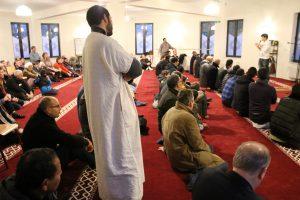 Un jeune musulman explique aux visiteurs (se trouvant à l'arrière) les gestes qui seront accomplis sous la conduite de l'imam.